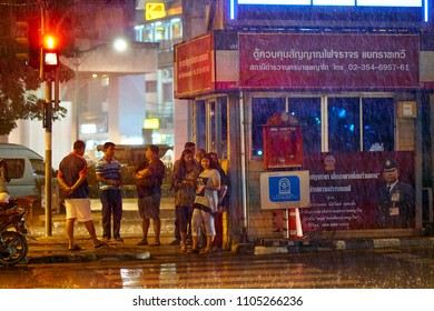 BANGKOK, THAILAND - July 15, 2017: People waiting for tropical heavy rain to stop. City streets in rainy weather.