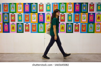 "Bangkok, Thailand - July 16 2019: A woman walking with motion blur in front of illustration gallery, at ""Lido Connect,"" a renovated vintage mall in Siam Square. The Grand Opening will be on 1 Aug 2019"