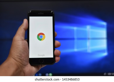 Bangkok, Thailand - July 17, 2019 : Gogle crome application on the Apple iPhone display screen. Top view of Business workplace.Closeup on a man's hands as he is using a smart phone