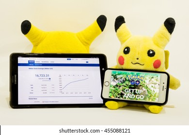 BANGKOK, THAILAND - JULY 19, 2016: A shot of Pikachu plushie with the web page of 'Pokemon Go' app and stock trend as the game has sent Nintendo and Nikkei stocks soaring since its first launch.