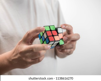 Bangkok, Thailand - July 19, 2018: Man wearing casual clothes collect Rubik's Cube. Rubik's cube invented by a Hungarian architect Erno Rubik in 1974.