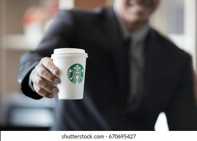 BANGKOK, THAILAND - JULY 2, 2017 : Businessman in suit holding Starbucks coffee cup in hand, Starbucks in the most popular premium coffee in Thailand