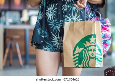 BANGKOK, THAILAND - JULY 2, 2017: Woman is holding Starbucks paper bag. Starbucks is an American coffee company and coffeehouse chain.