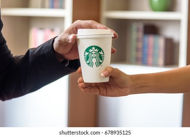 BANGKOK, THAILAND - JULY 2, 2017: woman hand giving Starbucks coffee cup to businessman hand