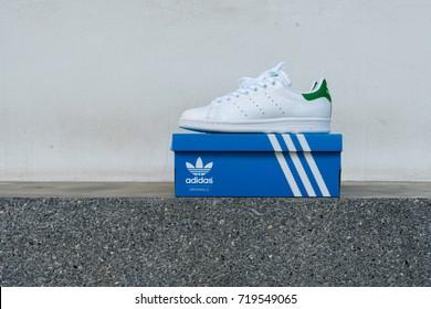BANGKOK, THAILAND - JULY 2, 2017: Open box adidas stan smith classic shoes on ground stone outdoor popular fashion thailand.