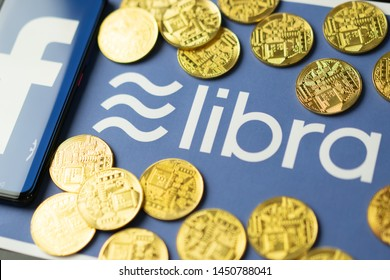 Bangkok, Thailand - July 2, 2019: Phone with Facebook logo on screen is placed on paper with Libra logo. Facebook reported to utilize new cryptocurrency called Libra expected to be used on Facebook.