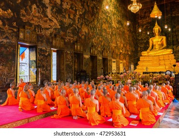 Bangkok, Thailand - July 20, 2016: Buddhist Monks praying and pay respect to the Buddha image at Wat Suthat on Buddhist Lent Day. The Buddhist Lent Day is The First Day of Rainy Season Retreat.