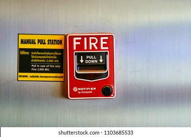 BANGKOK, THAILAND - July 20, 2017: Manual fire alarm pull station and sticker with instruction on Thai and English.