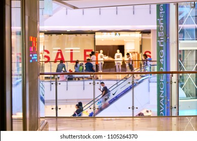 BANGKOK, THAILAND - July 20, 2017:  Out of focus crowded  shopping mall interior with sale sign in store window