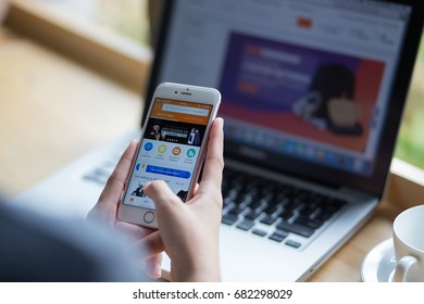 Bangkok. Thailand - July 20, 2017 : Women are typing on iphone 6s.  Like to shop online alibaba aliexpress app on the screen on desk office.  view of business workplace.
