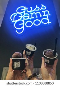 Bangkok, Thailand, July 20, 2018: photo of lady hands hold cups of Guss Damn Good ice cream(the famous ice cream shop in Thailand). Snap and share or camera eat first concept.