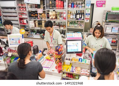 Bangkok, Thailand - July 20, 2019: cashiers work with customers at a 7-eleven convenience shop.