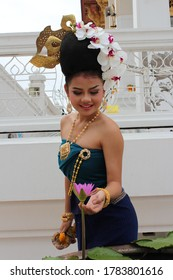 Bangkok ,Thailand - July, 2014:A Thai lady with Thai clothes in the northern style of Thailand wearing beauty designed stay in front of temple touching the lotus