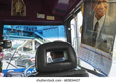 Bangkok, Thailand- July 21, 2017: A bus driver in Bangkok and calendars with picture of King Rama IX in the public bus.