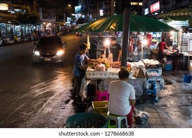 Bangkok, Thailand - July 21, 2018 : Traders selling goods by the sidewalk with their push carts next to the road at Huai Khwang night market