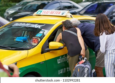 BANGKOK, THAILAND - July 22, 2017: Travelers negotiating a fare and ride details with local taxi driver in Bangkok.