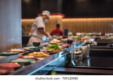 Bangkok, Thailand - July 22, 2017 : Unidentified chef cooking a food in the Japan food restaurant sushi conveyor or belt buffet for customer service in Thailand