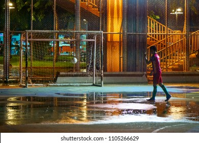 BANGKOK, THAILAND - July 23, 2017: Alone kid playing with a soccer football under evening rain on wet open air mini football pitch playground. Street sport activity concept.