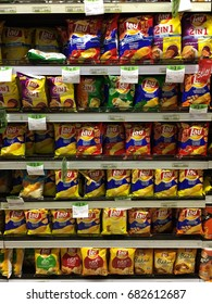 """BANGKOK, THAILAND - JULY 23, 2017: Different recipes of potato chips """"LAY"""" are displayed on several shelves in a shop."""