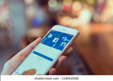 Bangkok, Thailand - July 23, 2018 : hand is pressing the Facebook screen on apple iphone6 ,Social media are using for information sharing and networking.