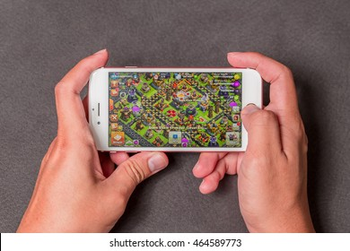 Bangkok, Thailand - July 24, 2016: Hand hold and playing Clash of Clans on an iPhone 6s running iOS. Clash of Clans is a popular online game in iPad/iPhone/iPod/Android game created by Supercell.