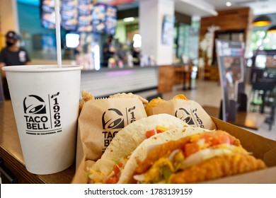 BANGKOK, THAILAND- JULY 24, 2020 : Box set of tasty taco, nachos, and cup of drink served in retail background of taco bell restaurant. A popular Mexican & American fast food chain. Selective focus.