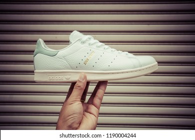 BANGKOK, THAILAND - JULY 27, 2018 : Hand holding Original Adidas Stan Smith shoes, sneakers, shows the logo on metal texture background. Sport and casual footwear concept.