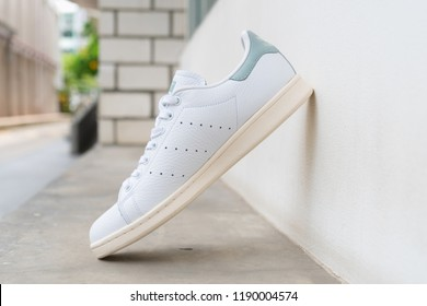 BANGKOK, THAILAND - JULY 27, 2018 : Original Adidas stan smith shoes, sneakers, shows the logo on street cement floor. Sport and casual footwear concept.