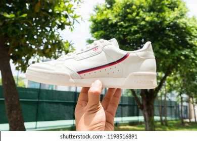 BANGKOK, THAILAND - JULY 27, 2018 : Hand holding Original Adidas Continental 80 Shoes , sneakers, shows the logo on nature background. Sport and casual footwear concept.