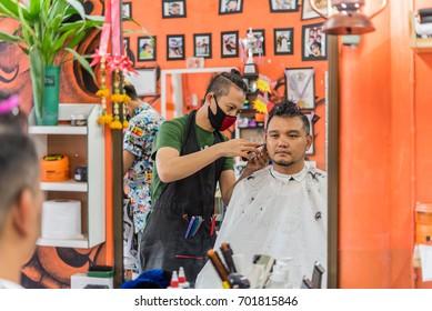 Bangkok, Thailand - July 28, 2017 : Unidentified Thai man barber haircut a man customer in fashion vintage hairstyle at barbershop