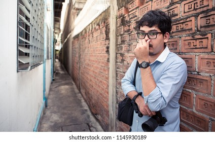 Bangkok, Thailand - July 28 2018: a young adult man holding DSLR camera as mature journalist photographer standing in very narrow street of Bangkok alley with poor street design by government