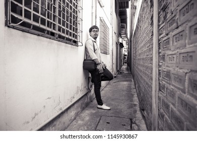 Bangkok, Thailand - July 28 2018: Black and white a young adult man standing in very narrow street of Bangkok alley with poor street design by government, the street is too narrow for people