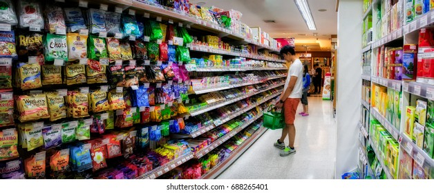BANGKOK, THAILAND - July 28: An Unidentified man shops for candy in the sweets aisle of Foodland Supermarket on July 28, 2017 in Bangkok.
