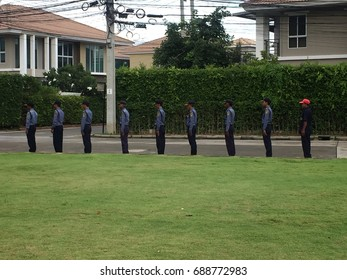 BANGKOK, THAILAND - JULY 30, 2017: A group of guards wearing same uniforms has a brief meeting outdoor, and the supervisor wearing different clothes stands at the top of the line.