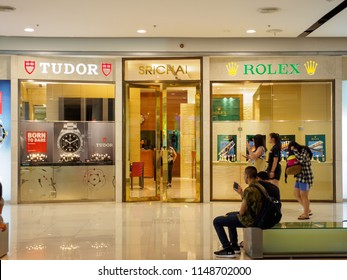 BANGKOK, THAILAND - July 30, 2018: Tourists sit in front of and walk past a Rolex and Tudor authorized dealer at Central World department store. Luxury watches and fashion industry.