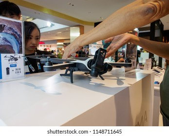 BANGKOK, THAILAND - July 30, 2018: A customer reaches and holds a GoPro Karma video recording drone during a camera fair at Central World Department store. Photographic equipment industry.