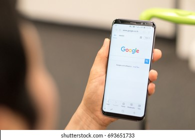 BANGKOK, THAILAND - July 4, 2017: Hands using smartphone Samsung Galaxy S8 with Google search engine on web page app