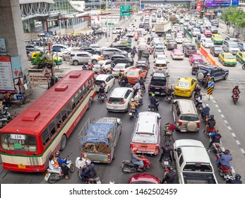 BANGKOK, THAILAND - July 4, 2019 : Many cars and motorbikes are stop and wait for the green traffic sign at the four junctions at Ratchadaphisek road nearby Phetchaburi MRT Station, Bangkok, Thailand.