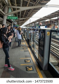 Bangkok, Thailand - July 4,2019: People stand behind the yellow line waiting BTS Skytrain.
