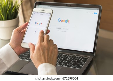 BANGKOK, THAILAND. July 6, 2017: Google search engine sign up page on mobile app touchscreen on iphone in business person's hand and on computer screen display