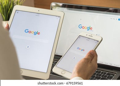 BANGKOK, THAILAND. July 6, 2017: Google search engine sign-in page on mobile app touchscreen on ipad, iphone in business person's hand and on computer screen display