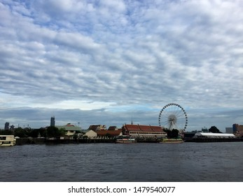 Bangkok, Thailand - July 6, 2019:A landscape view of Ferris Wheel in ASIATIQUE The Riverfront with a few river shuttle water bus cruising the Chao Phraya River and blue sky in Bangkok. - Image