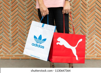 BANGKOK, THAILAND - JULY 7, 2018 : A woman wearing Nike t -shirt and sweatpants holding shopping bag Adidas and Puma on street with red brick wall background