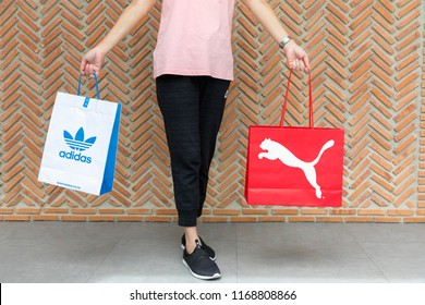 BANGKOK, THAILAND - JULY 7, 2018 : A woman wearing Nike t -shirt, sweatpants and New balance slip on shoes and holding shopping bag Adidas and Puma on street with red brick wall background