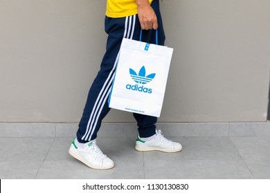 BANGKOK, THAILAND - JULY 7, 2018:A man holding paper bag Adidas original logo for product Adidas original. Adidas - German industrial group specializing in the production of athletic footwear, apparel