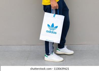 dbef9808e8 BANGKOK, THAILAND - JULY 7, 2018:A man holding paper bag Adidas original