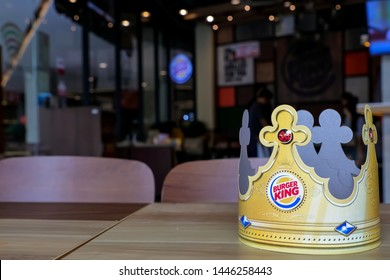 Bangkok, Thailand - July 7, 2019 :  Burger King paper crown on wooden table, Blurred atmosphere in fast food restaurant.