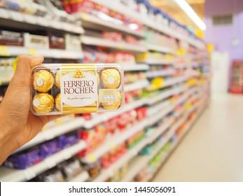 BANGKOK, THAILAND - JULY 7,2019 : Hand holds Ferrero Rocher premium chocolate, Ferrero Rocher is a spherical chocolate produced by the Italian chocolatier Ferrero SpA, Shopping concept.