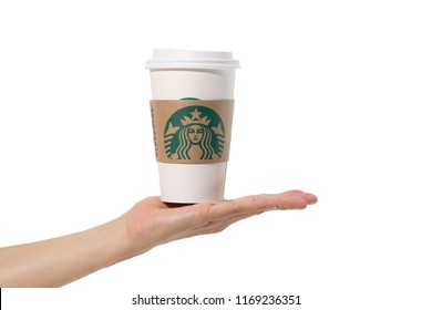 Bangkok, Thailand - July 8, 2018: Female hands holding a cup of Starbuck coffee on white background