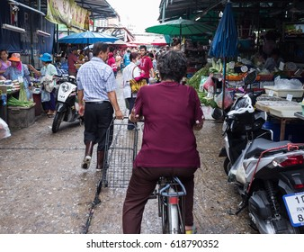 BANGKOK, THAILAND- JULY 9, 2015: Khlong Toei food market. Local Thai senior woman on the bike in the crowd from behind